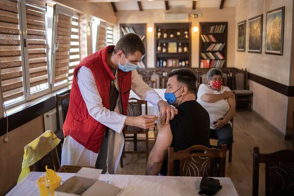 Un uomo si vaccina contro il COVID-19 in un ristorante serbo. I clienti potranno ricevere un pasto gratis dopo aver ricevuto il vaccino.  - Sputnik Italia