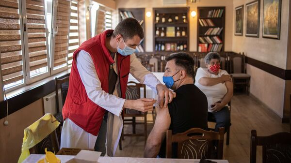 Мужчина получает дозу китайской вакцины Sinopharm против коронавирусной болезни (COVID-19) в ресторане в Крагуеваце, Сербия - Sputnik Italia