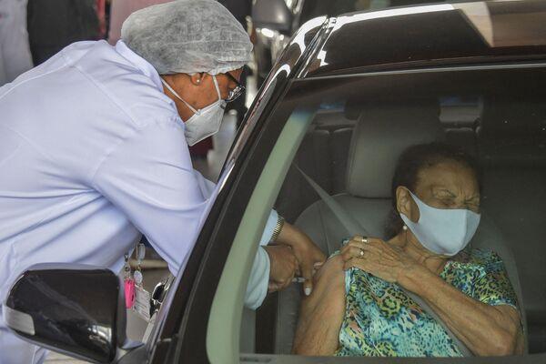 Una donna anziana brasiliana riceve il preparato CoronaVac della compagnia cinese SinoVac in un centro di vaccinazione drive-through.  - Sputnik Italia