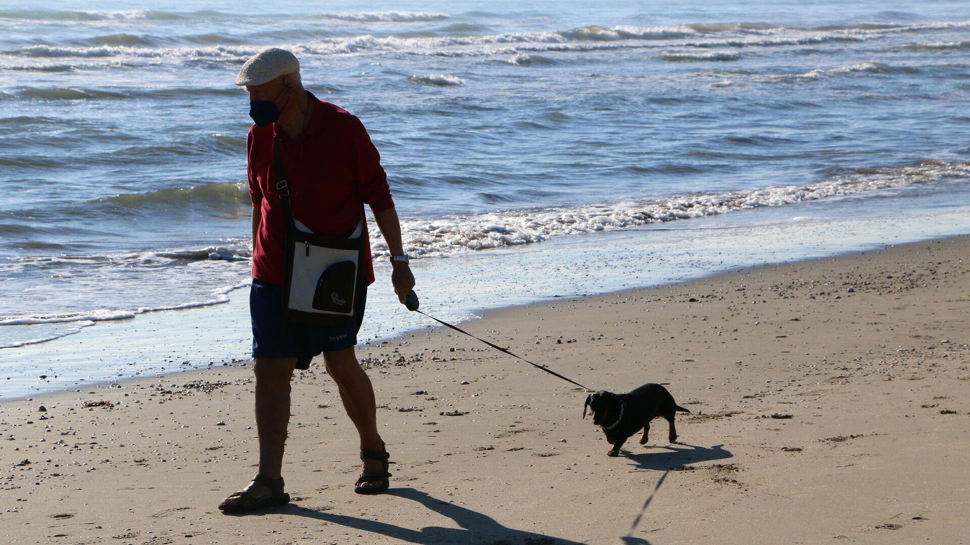 Un uomo con il suo cane passeggia lungo la costa del mare - Sputnik Italia, 1920, 07.06.2021