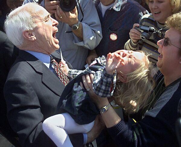 Il candidato alle presidenziali dei repubblicani, John McCain, tiene in braccio una bambina piangente durante la manifestazione alla Furman University, 16 febbraio 2000 a Greenville, nella Carolina del Sud, USA.  - Sputnik Italia