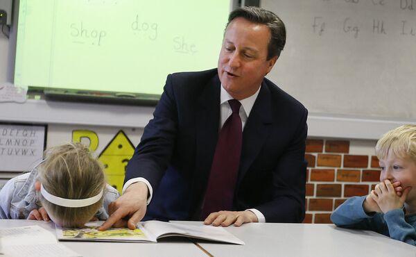 Il primo ministro britannico David Cameron legge un libro alle bambine Lucy Howarth e Joshua Davies durante la sua visita alla scuola primaria Sacred Heart RC a Westhoughton vicino a Bolton, 8 aprile 2015, Gran Bretagna.  - Sputnik Italia