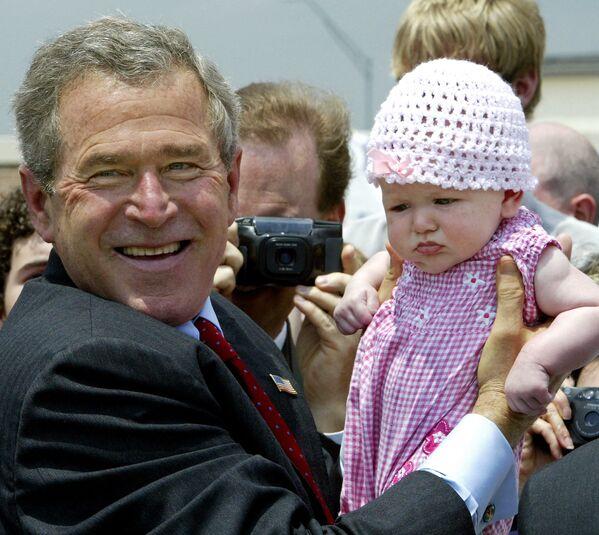 L'ex presidente degli Stati Uniti George W. Bush tiene in braccio un bambino di tre mesi del nome Emmalee Hibbs dopo il discorso rivolto ai suoi sostenitori all'aeroporto regionale di Fort Smith, 11 maggio 2004, USA - Sputnik Italia