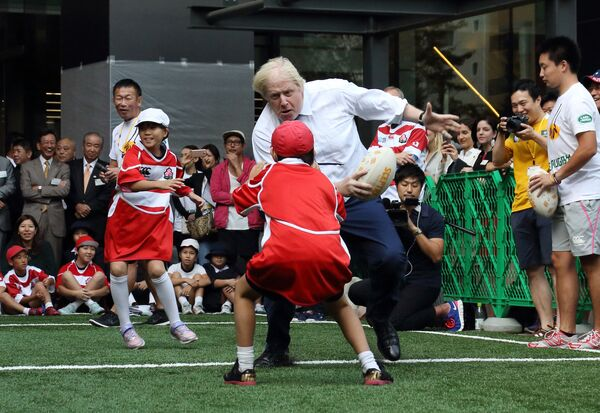 Il sindaco di Londra Boris Johnson gioca a rugby con i bambini delle scuole elementari giapponesi a Tokyo, 15 ottobre 2015 - Sputnik Italia
