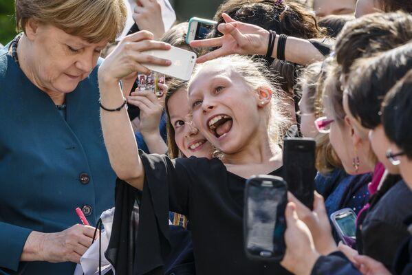 La cancelliera tedesca Angela Merkel firma autografi mentre gli studenti cercano di fare dei selfie con lei durante la sua visita alla scuola Lycee Francais di Berlino, 3 maggio 2016. - Sputnik Italia