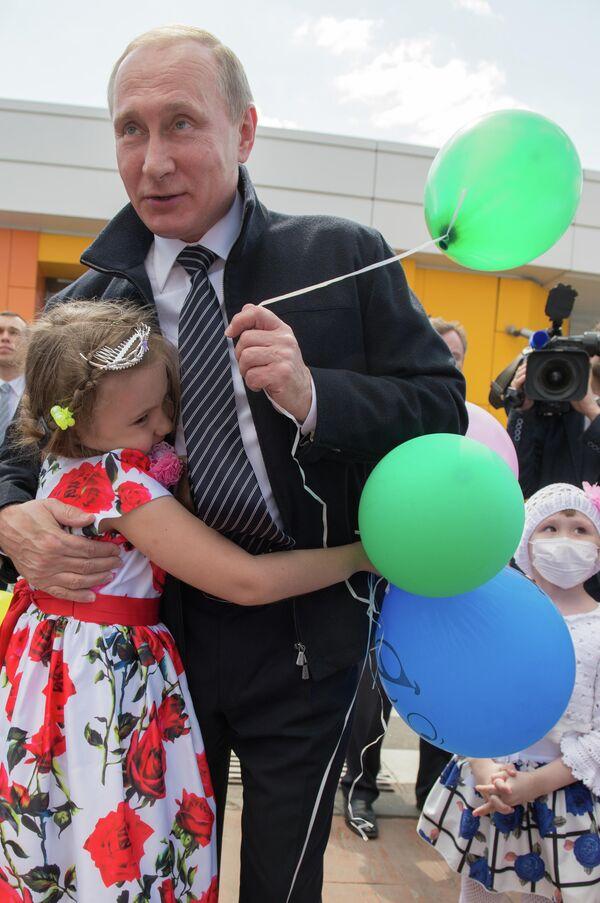 Il presidente russo Vladimir Putin abbraccia una bambina durante la sua visita al Centro di ematologia infantile a Mosca, 1 giugno 2016.  - Sputnik Italia