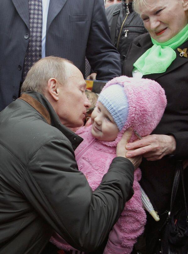 Il presidente russo Vladimir Putin bacia una bambina durante la sua visita nel villaggio di Nevskaya Dubrovka, 29 maggio 2010 - Sputnik Italia