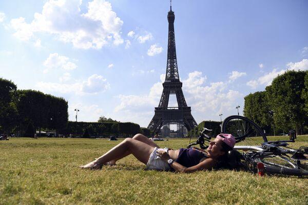 Una donna si gode una giornata calda nel giardino Champ-de-Mars vicino alla Torre Eiffel a Parigi, 25 giugno 2020. - Sputnik Italia