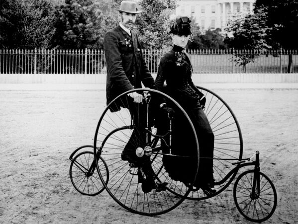 Una coppia vestita in modo elegante va sul quadriciclo a pedali per due persone (modello 1886) sullo sfondo del portico sud della Casa Bianca, Washington, D.C. - Sputnik Italia