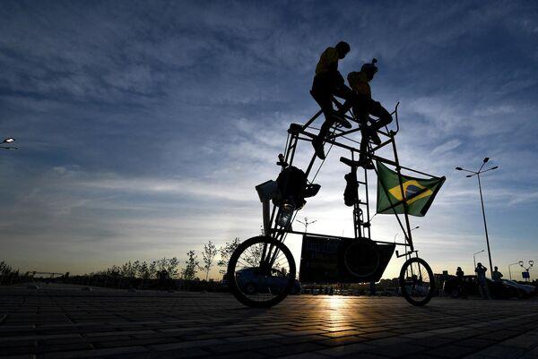 I tifosi brasiliani Elias de Souza e suo figlio Elias de Souza junior vanno in bicicletta tandem alta 3 metri vicino all'Arena di Rostov a Rostov sul Don durante il Campionato mondiale di calcio 2018 in Russia. - Sputnik Italia