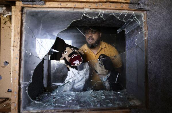 Mohammed Saed, un comico palestinese, fondatore di Beit al-Fann (la casa dell'arte) a Gaza City, mostra i burattini che ha recuperato dal loro studio, danneggiato durante il bombardamento israeliano, il 29 maggio 2021. - Sputnik Italia