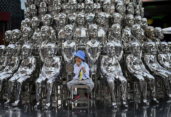 Un bambino siede su una sedia tra le sculture in mostra in un centro commerciale in occasione della Giornata internazionale dei bambini a Pechino il 1° giugno 2021, un giorno dopo che la Cina ha annunciato che avrebbe permesso alle coppie di avere tre figli. - Sputnik Italia