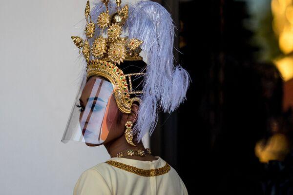 Una ballerina tradizionale thailandese che indossa una visiera protettiva facciale in plastica si prepara ad esibirsi al Museo Nazionale di Bangkok, il 31 maggio 2021. - Sputnik Italia