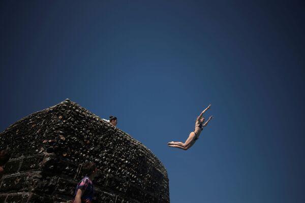 Una donna si tuffa nel mare mentre le persone si godono il sole sulla spiaggia di Brighton, Gran Bretagna. - Sputnik Italia