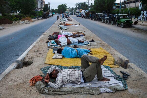 I lavoratori dormono lungo una strada nella città portuale di Karachi il 1° giugno 2021. - Sputnik Italia