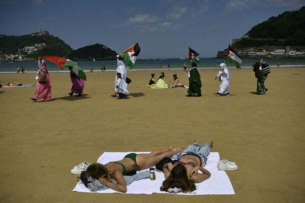 Le persone con le bandiere prendono parte a una manifestazione lungo la spiaggia della Concha per sostenere Brahim Ghali, leader del Fronte Polisario per la liberazione del Sahara Occidentale, a San Sebastian, nel nord della Spagna, domenica 30 maggio 2021.  - Sputnik Italia