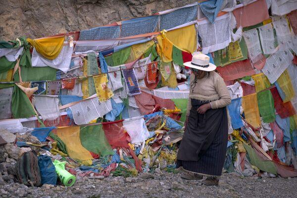 Una donna tibetana passa davanti alle bandiere di preghiera vicino al lago sacro Namtso, nella regione del Tibet, nella Cina occidentale, mercoledì 2 giugno 2021. - Sputnik Italia