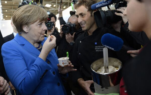La cancelliera tedesca Angela Merkel assaggia il gelato che le è stato offerto dal gelatiere Italiano di origini cadorine Adriano Colle, durante la visita alla fiera Internationale dell'Artigianato Handwerksmesse a Monaco di Baviera, nel sud della Germania, il 13 marzo 2015. - Sputnik Italia