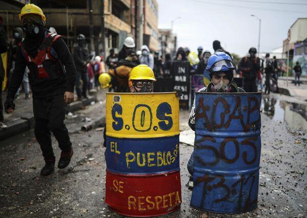 I manifestanti anti-governativi si nascondono dietro gli scudi improvvisati durante gli scontri con la polizia a Bogotà, in Colombia, mercoledì 9 giugno 2021.  - Sputnik Italia
