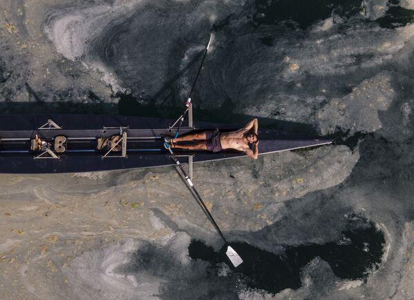 Un uomo si rilassa su una canoa sulla costa di Caddebostan, nella parte asiatica di Istanbul, circondato da un'enorme massa di mucillagine marina nel Mar di Marmara in Turchiaб martedì 8 giugno 2021. - Sputnik Italia
