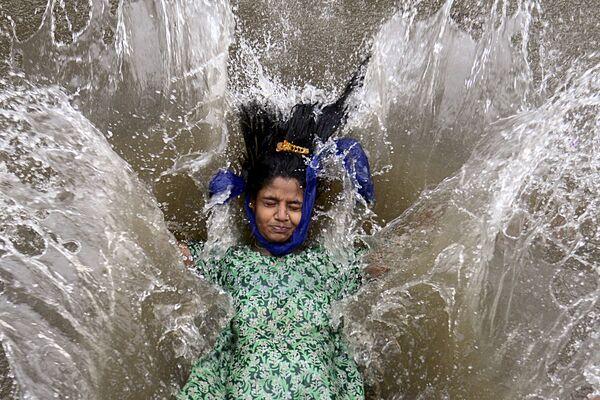Una ragazza gioca in una strada allagata a seguito di una forte pioggia monsonica a Mumbai il 9 giugno 2021. - Sputnik Italia