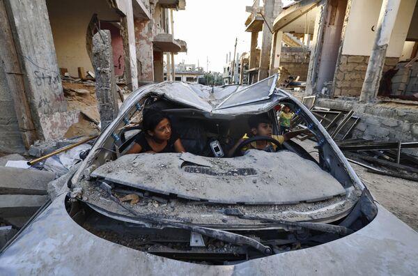 Bambini palestinesi giocano all'interno di un'auto distrutta durante il conflitto del maggio 2021 tra Hamas e Israele, a Beit Hanun, nel nord della Striscia di Gaza, il 7 giugno 2021. - Sputnik Italia