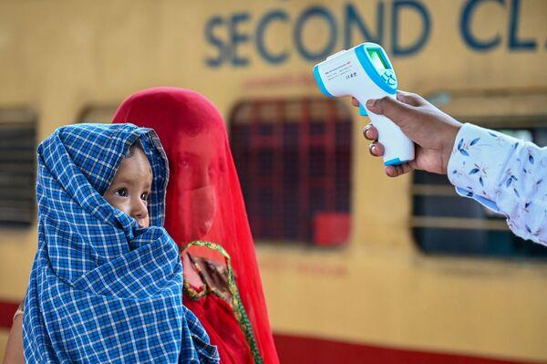 Un operatore sanitario controlla la temperatura di una passeggera alla stazione ferroviaria a Mumbai l'8 giugno 2021. - Sputnik Italia