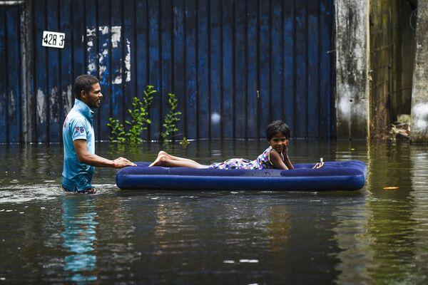 Un uomo spinge un bambino sdraiato su un materasso gonfiabile dopo le forti piogge monsoniche a Kelaniya, alla periferia di Colombo, il 6 giugno 2021. - Sputnik Italia