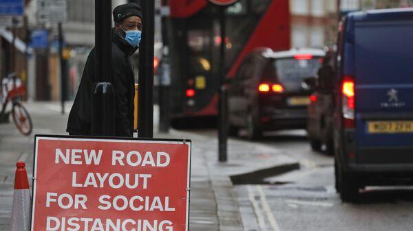 Мужчина в маске ждет рядом с вывеской, информирующей о новой схеме дороги для социального дистанцирования, в Лондоне, Англия - Sputnik Italia