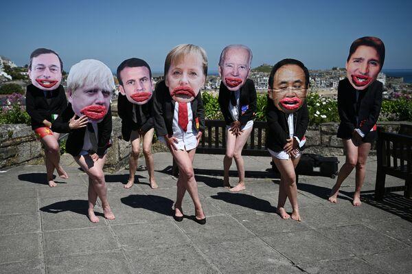 Gli attivisti ambientali di Extinction Rebellion con le foto dei volti dei leader del G7 in una manifestazione contro la disuguaglianza di genere in politica a St Ives, in Cornovaglia, durante il vertice del G7 il 13 giugno 2021.  - Sputnik Italia