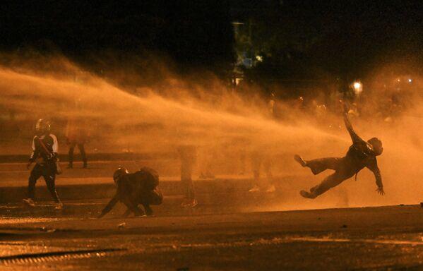 Un manifestante cade colpito da un cannone ad acqua durante gli scontri con la polizia antisommossa tra le proteste in corso contro il governo del presidente colombiano Ivan Duque a Bogotà il 12 giugno 2021.  - Sputnik Italia