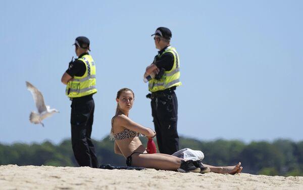 Una donna prende il sole, mentre la polizia è in pattuglia nelle vicinanze durante l'incontro dei leader del G7 che si è svolto a St. Ives, in Cornovaglia, in Inghilterra, sabato 12 giugno 2021. - Sputnik Italia