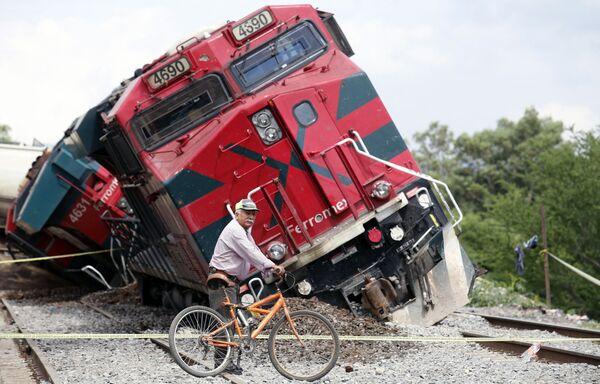 Un uomo con una bicicletta passa accanto a un treno che è deragliato nella comunità di San Isidro Mazatepec a Tala, nello stato di Jalisco, in Messico, il 15 giugno 2021.  - Sputnik Italia