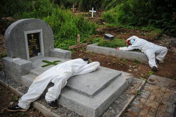 I lavoratori che indossano tute protettive riposano dopo aver seppellito una vittima della malattia di coronavirus (COVID-19) a Bandung, provincia di West Java, Indonesia, il 15 giugno 2021. - Sputnik Italia