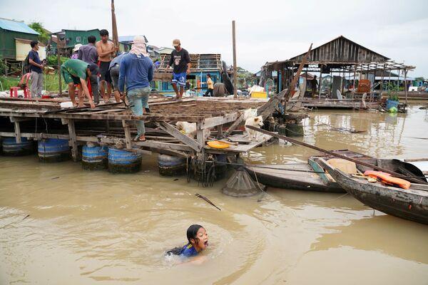 I residenti demoliscono le loro case galleggianti sul fiume Tonle Sap dopo che è stato ordinato a loro di andarsene entro una settimana dalla notifica da parte delle autorità locali nel distretto di Prek Pnov, Phnom Penh, Cambogia, il 12 giugno 2021. - Sputnik Italia