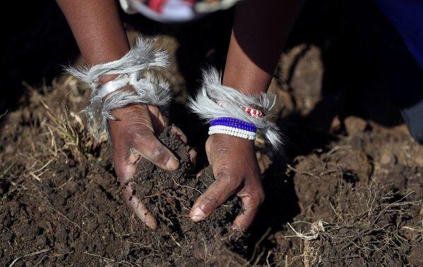 Una donna con la pelle di animale sulle mani ispeziona il terreno. - Sputnik Italia