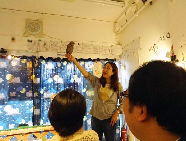 Un dipendente di Fukuro no Mise, che significa Negozio dei Gufi, a Tokyo, che mostra il modo corretto di tenere in mano un gufo. - Sputnik Italia
