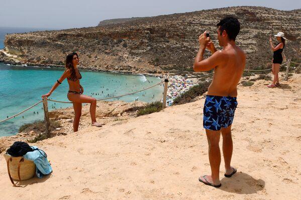I turisti scattano delle foto sulla spiaggia, Lampedusa, Italia, il 22 giugno 2021. - Sputnik Italia