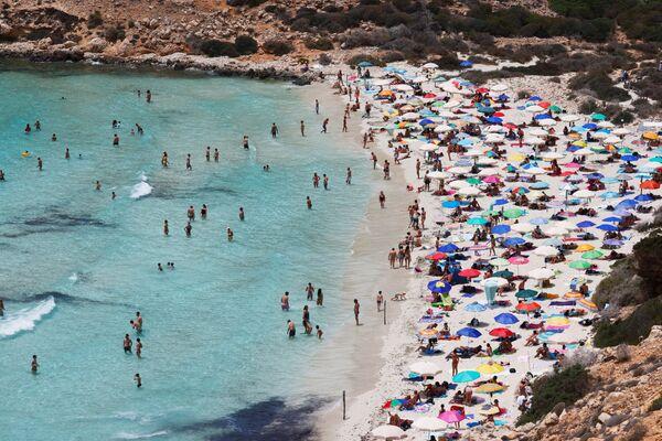 La gente prende il sole sulla spiaggia dell'isola siciliana di Lampedusa, Italia, il 22 giugno 2021. - Sputnik Italia