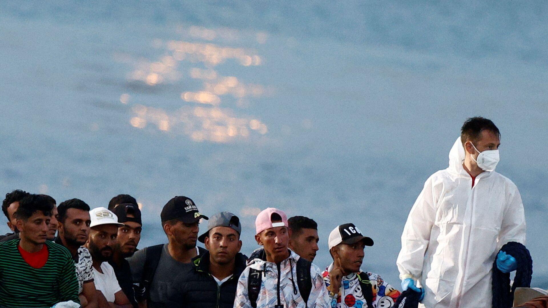Мигранты сидят в итальянском катере береговой охраны перед высадкой на сицилийском острове Лампедуза, Италия - Sputnik Italia, 1920, 14.07.2021