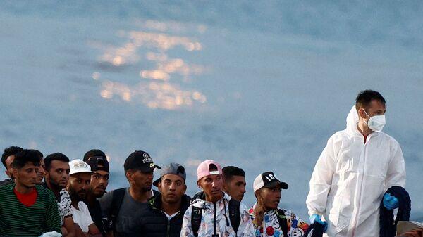 Мигранты сидят в итальянском катере береговой охраны перед высадкой на сицилийском острове Лампедуза, Италия - Sputnik Italia
