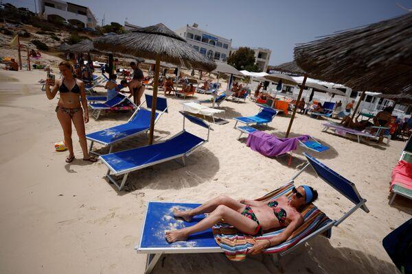 Le autorità invitiano i turisti e i bagnanti a non accedere quando verrà esposto l'avviso di 'spiaggia piena' per evitare assembramenti e di occupare aree vietate. - Sputnik Italia
