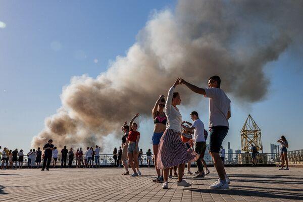 Coppie ballano samba sullo sfondo della colonna di fumo che sale da un magazzino pirotecnico in fiamme a Mosca il 19 giugno 2021. - Sputnik Italia