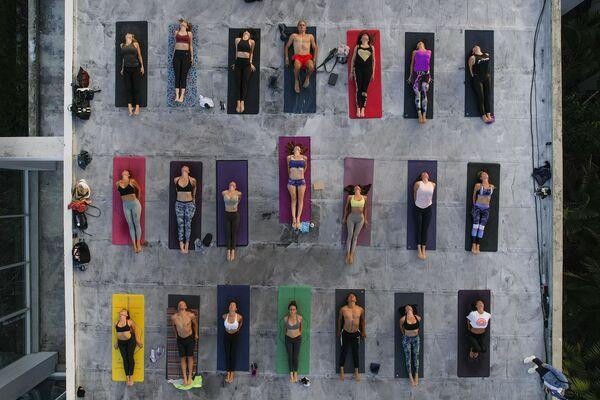 Gli appassionati praticano lo yoga in occasione della Giornata internazionale dello yoga, mantenendo il distanziamento sociale come previsto dalle misure anti-contagio contro pandemia COVID-19, sul tetto dello studio ARA Yoga Caracas a Caracas, Venezuela, lunedì 21 giugno 2021. - Sputnik Italia
