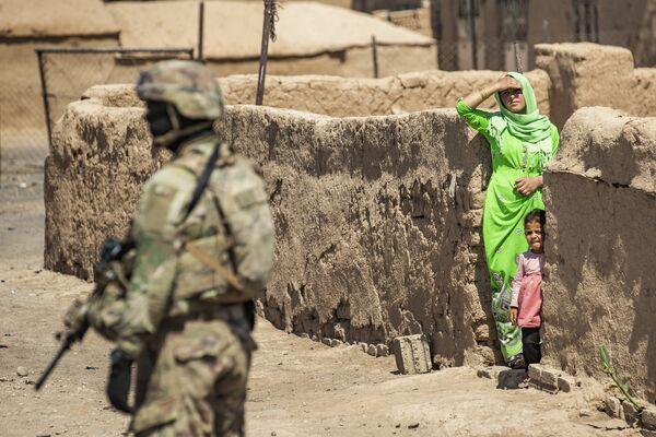 Un soldato americano pattuglia le strade mentre una residente locale con un bambino lo osservano, Rumaylan (Rmeilan), provincia nordorientale di Hasakeh, in Siria, il 22 giugno 2021 - Sputnik Italia
