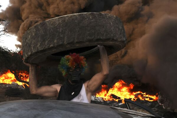 Palestinesi bruciano pneumatici durante una manifestazione notturna contro l'espansione dell'avamposto ebraico di Eviatar sulle terre del villaggio di Beita, vicino alla città occupata di Nablus, in Cisgiordania, il 23 giugno 2021. - Sputnik Italia
