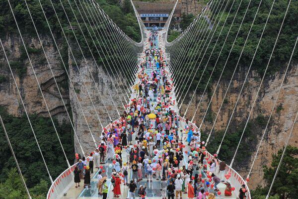 La foto scattata il 20 giugno 2021 mostra persone camminare per un ponte di vetro a Zhangjiajie, nella provincia centrale di Hunan in Cina. - Sputnik Italia