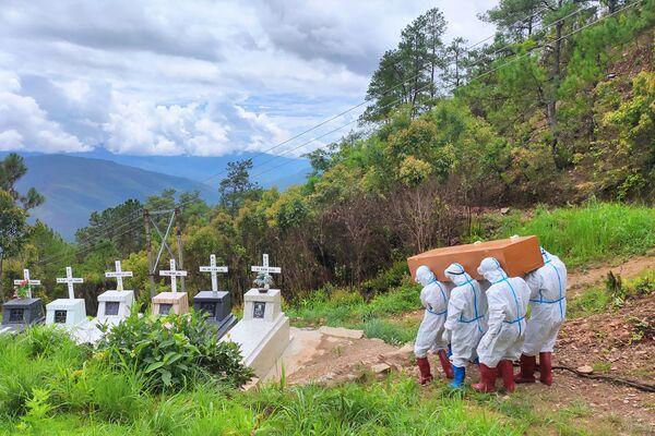 La foto del gruppo di media locali Chinland Herald Daily News, scattata il 21 giugno 2021 e pubblicata il 22 giugno, mostra operatori sanitari in tuta protettiva trasportare una bara con il corpo di un paziente con coronavirus Covid-19 durante una sepoltura in un cimitero a Falam cittadina nello stato Chin del Myanmar occidentale. - Sputnik Italia