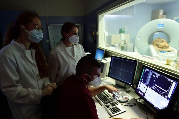 Tecnici e ricercatori di radiologia medica guardano lo schermo di un computer mentre la mummia egizia viene sottoposta alla scansione TAC con lo scopo di scoprire la sua storia presso l'ospedale Policlinico di Milano. - Sputnik Italia
