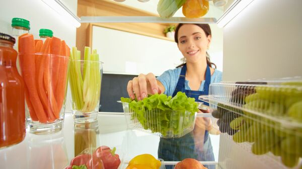Девушка перед открытым холодильником с овощами и фруктами - Sputnik Italia